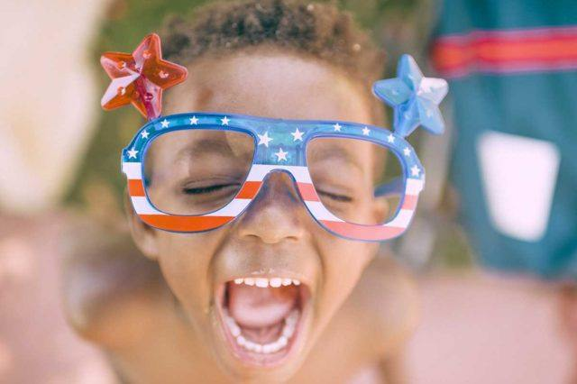 a young boy with patriotic sunglasses is yelling outside on a bright day