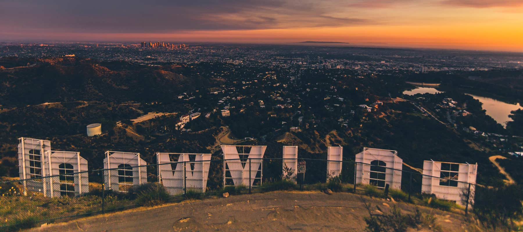 view of los angeles from behind the hollywood sign at dusk