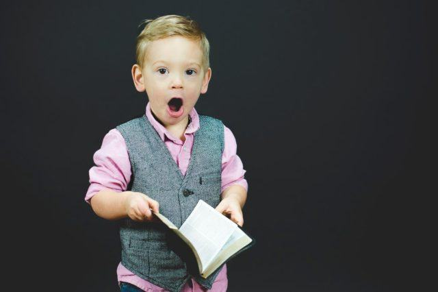 little boy in suit vest with shocked expression while holding book